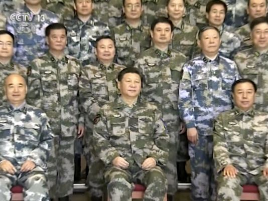 In this April 21, 2016, image taken from a video footage run by China's CCTV via AP Video, Chinese President Xi Jinping, center, in military uniform poses for a group photo with military staff members at the Chinese army's Joint Operation Command Center in Beijing. Xi is assuming a more direct role as commander of the country's powerful armed forces with the new title of commander in chief of its Joint Operations Command Center. Xi's new position was revealed in news reports run on Wednesday and Thursday in which he appeared publicly for the first time in camouflage battle dress wearing the center's insignia.(Photo: CCTV via AP) http://www.militarytimes.com/story/military/2016/04/21/chinas-xi-moves-take-more-direct-command-over-military/83339516/