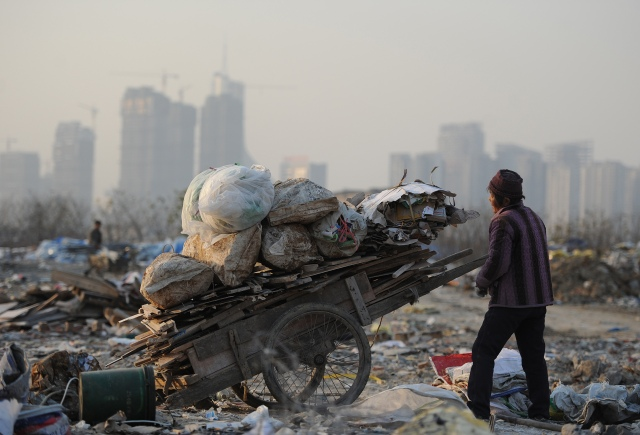 This picture taken on December 9, 2012 shows scavengers picking up useful construction waste from a garbage dump in Hefei, central China's Anhui province.  China's wealth gap has widened to a level where it is among the world's most unequal nations, a Chinese academic institute said in a survey, as huge numbers of poor are left behind by the economic boom. CHINA OUT     AFP PHOTO        (Photo credit should read STR/AFP/Getty Images)